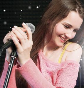 Girl singing with microphone in pink off the shoulder sweater looking down to the right
